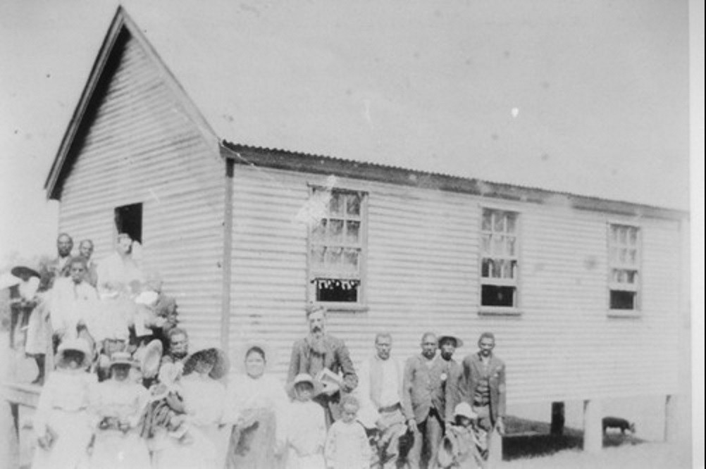 Australian South Sea Islanders standing outside a church in Joskeleigh Queensland ca 1913 Photographer unknown John Oxley Library State Library of Queensland Image no 28873-0001-0150