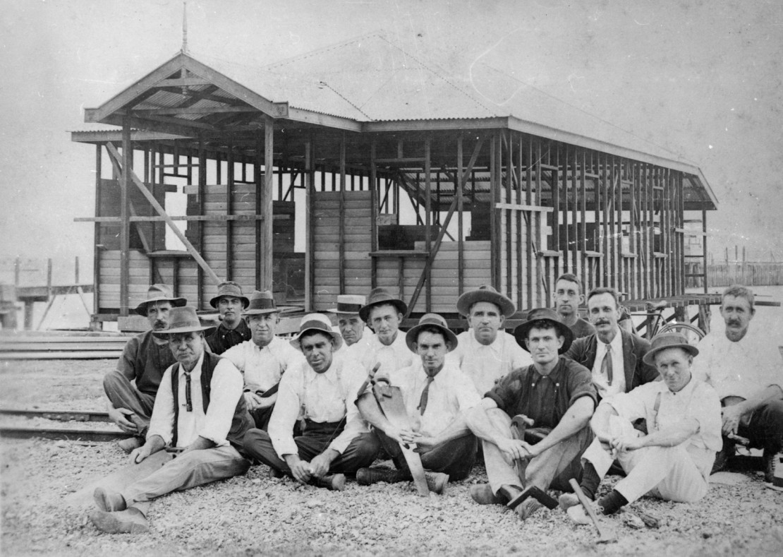 A group of men out the front of a house they are building