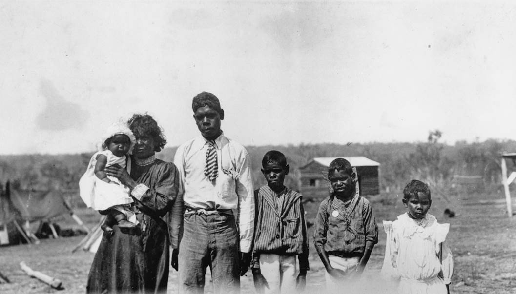 An Aboriginal family with four children standing at a camp site