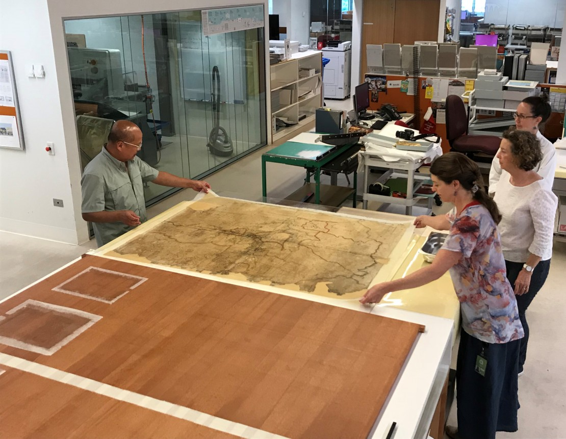 Conservators Eddie Jose and Jennifer Loubser transfer the map onto karibari for flattening