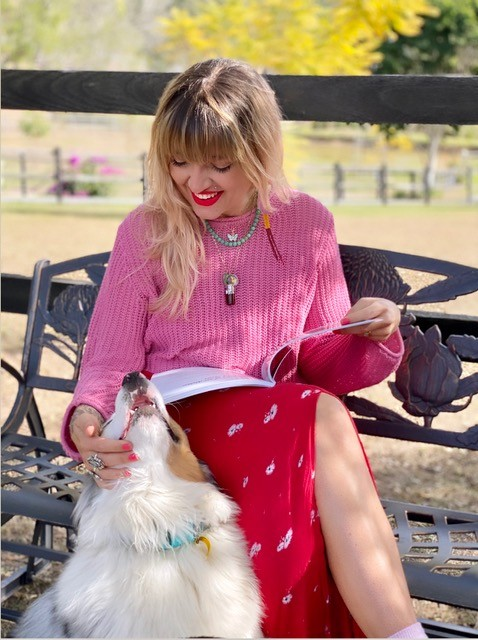 A woman sitting on an ornate metal bench with a book open in her lap A dog sits on the ground next to her she is smiling down at it while she pats it