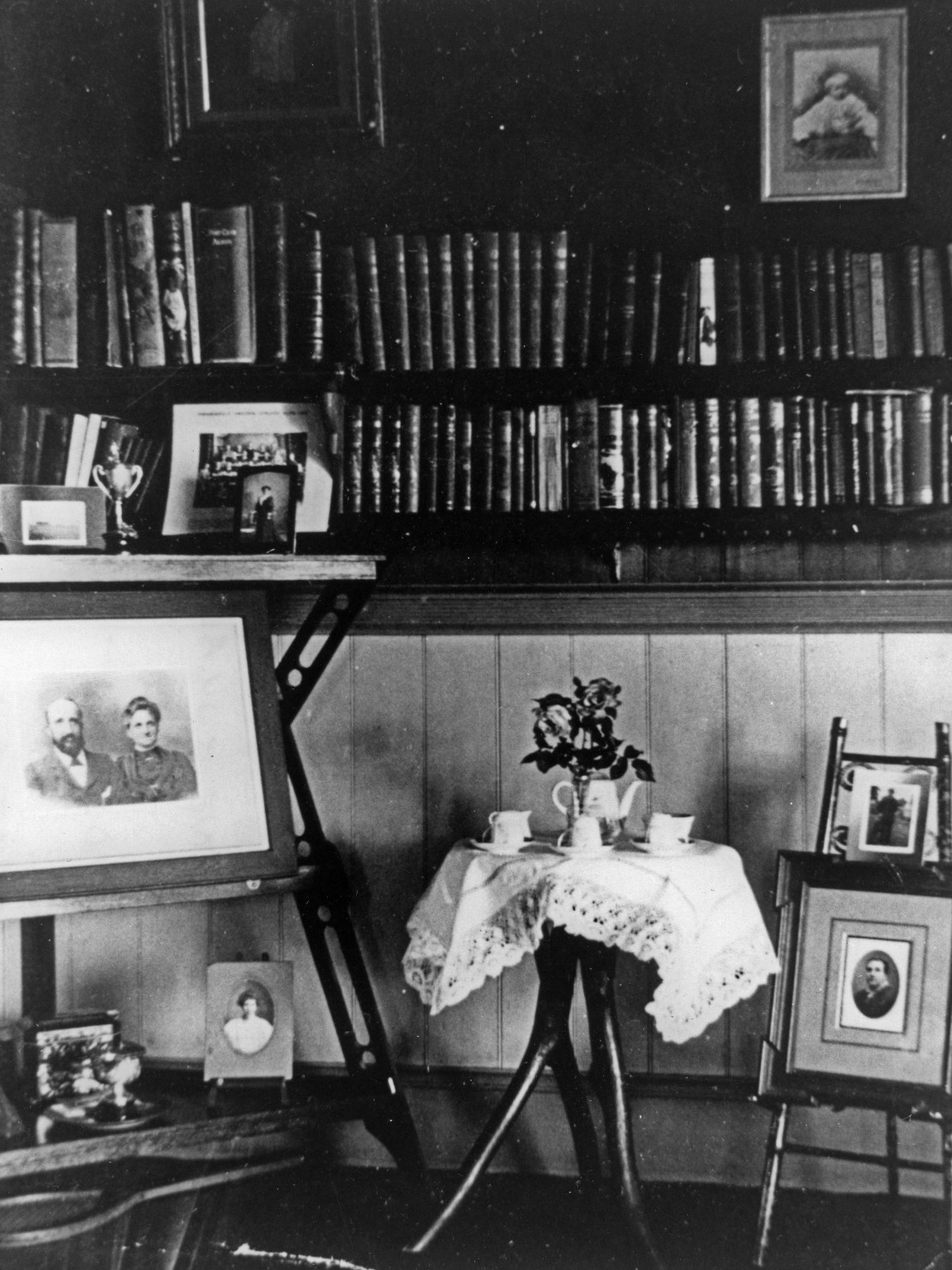 Interior view of a house at Indooroopilly showing a collection of books and family photographs  There is a small table in the centre covered with a lace tablecloth set with teacups and saucers