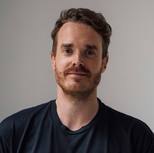 Photo of Jack Vening wearing a navy blue t-shirt against a grey background