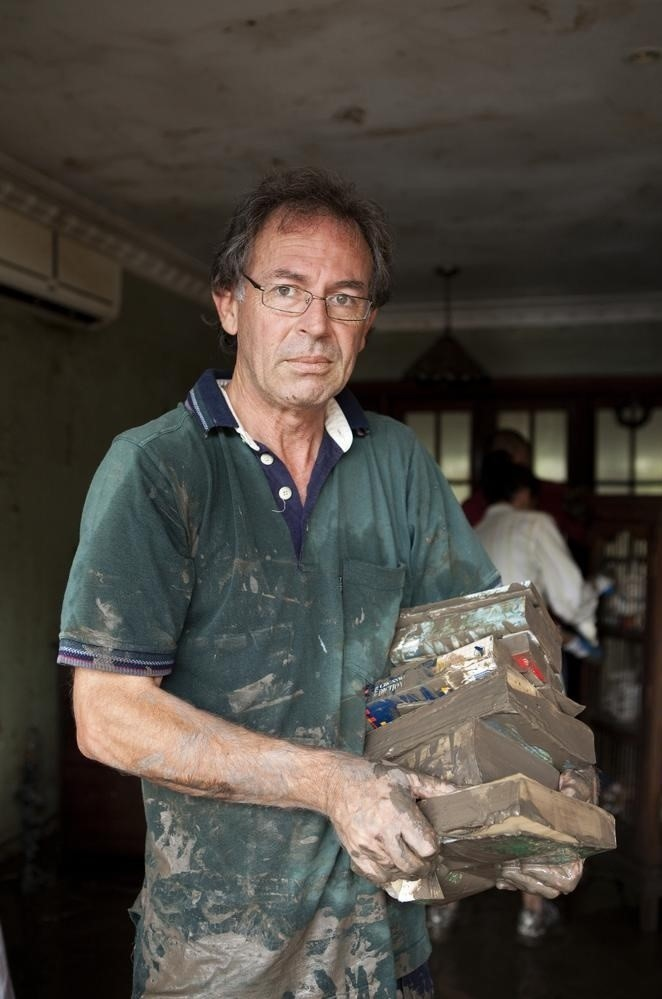 John Bellas carrying ruined books in his flooded home at Fairfield 2011
