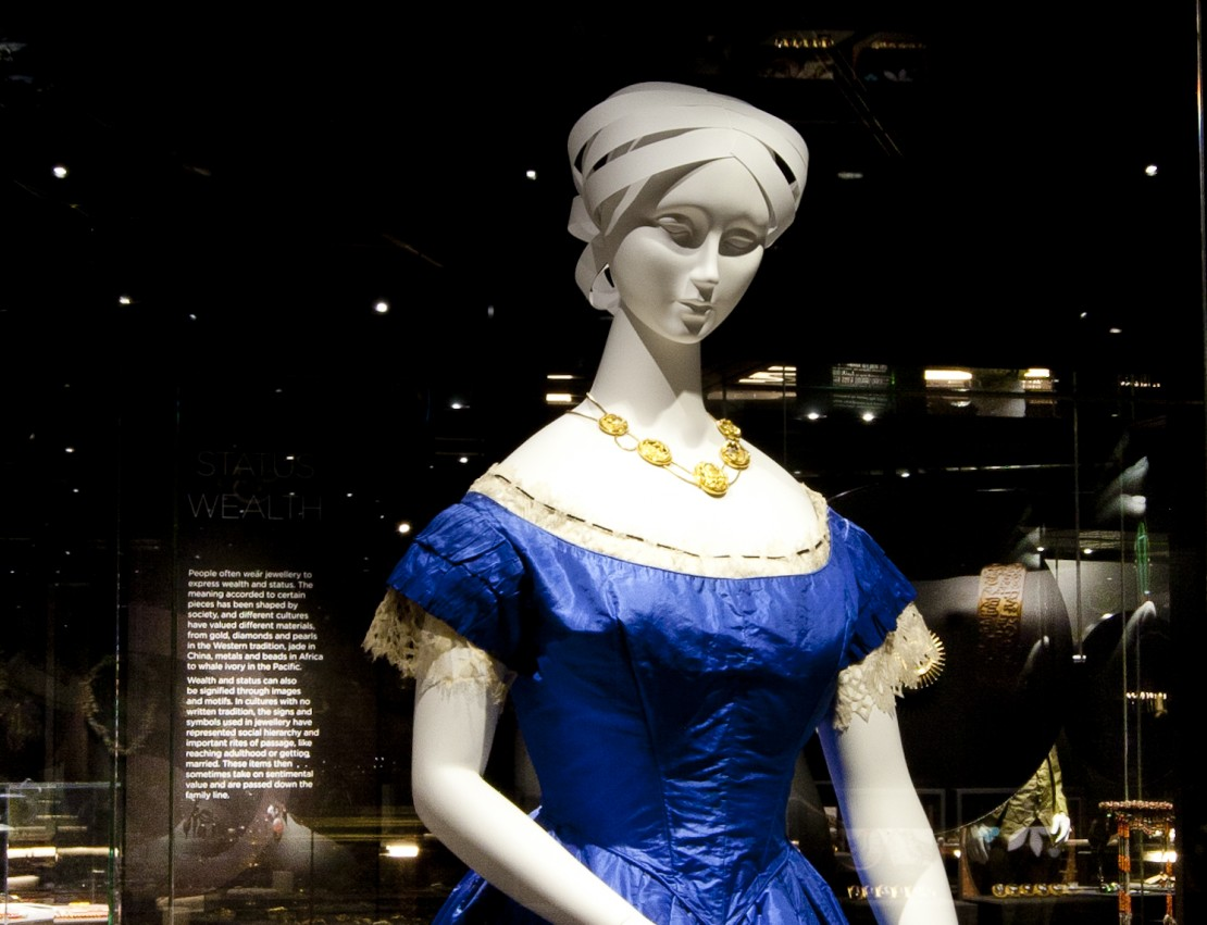 Mannequin in a blue dress wearing the John Watts Necklace as seen in the 2014 exhibition A Fine Possession Jewellery and Identity The necklace is an 18 carat gold swag necklace with five openwork carved gold hinged pendants