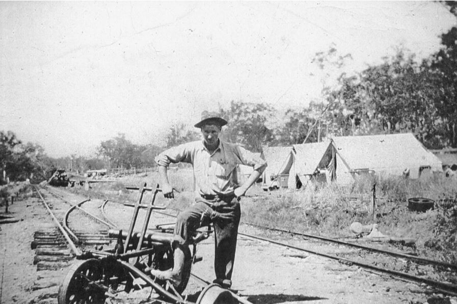 Black and white photo of a railway worker leaning on his trolley on the railway line with tents in the background