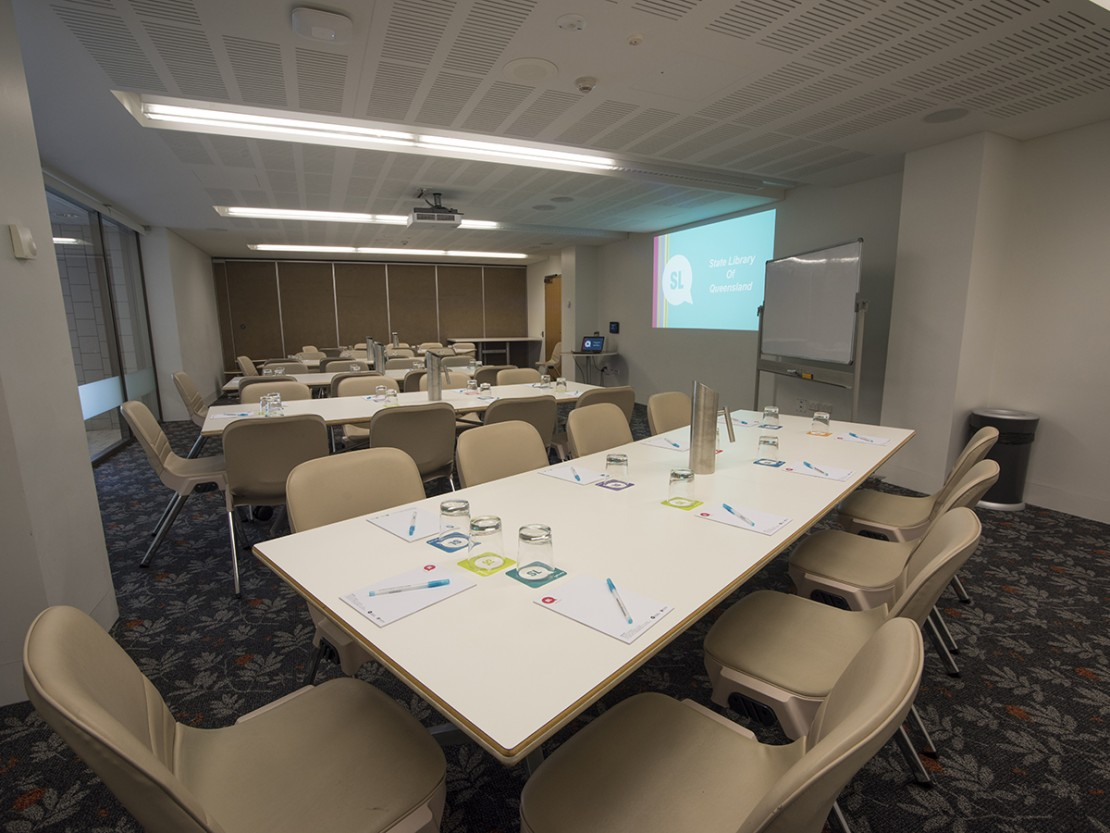 Meeting room 1B with tables whiteboard and projector