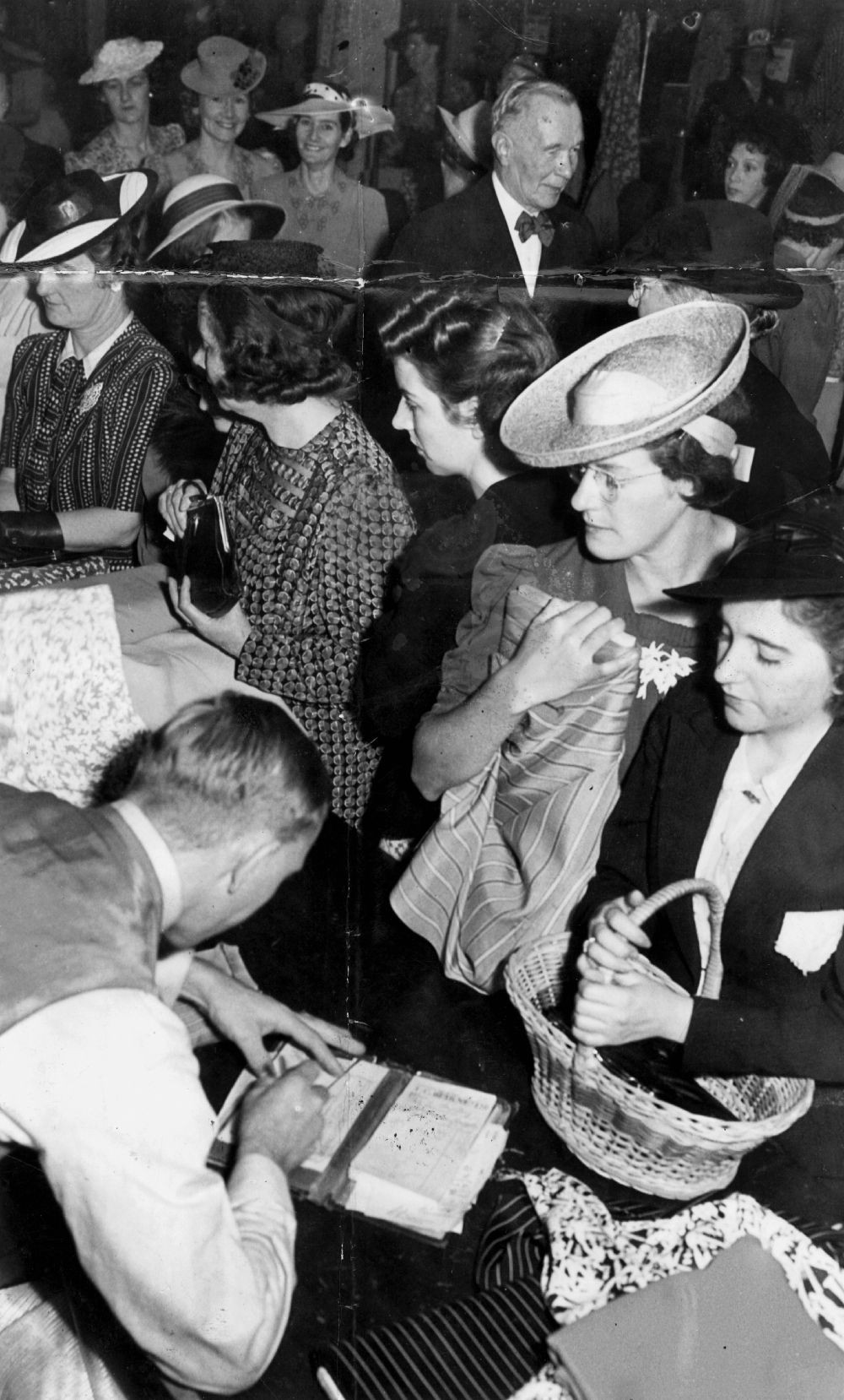 A group of women at a shop counter with a man serving them and writing in a receipt book