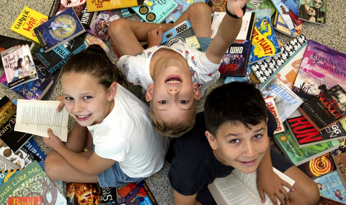 A girl and two boys surrounded by a pile of books