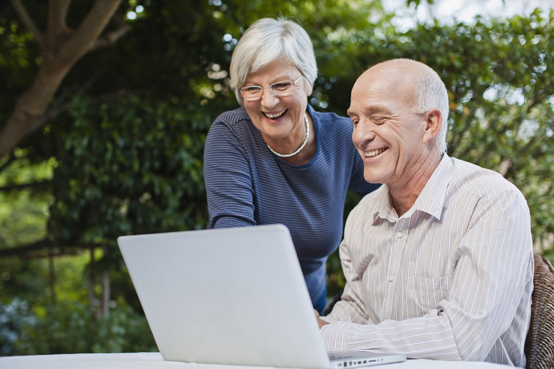 An older people sitting in front of a laptop