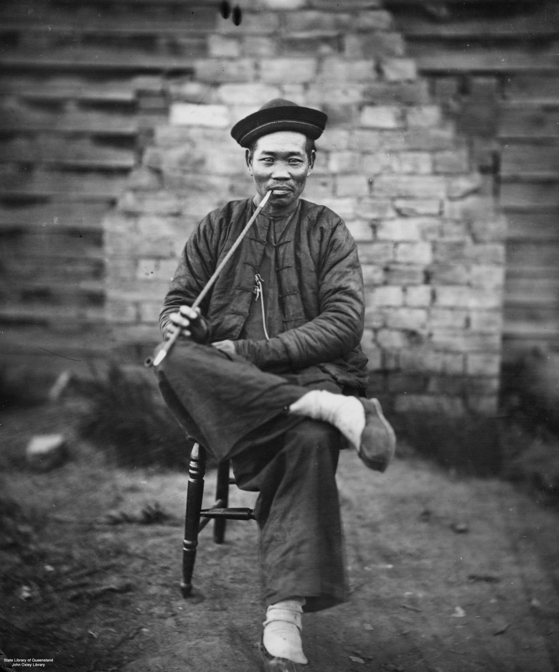 Chinese miner in traditional garb relaxing with a long stemmed pipe