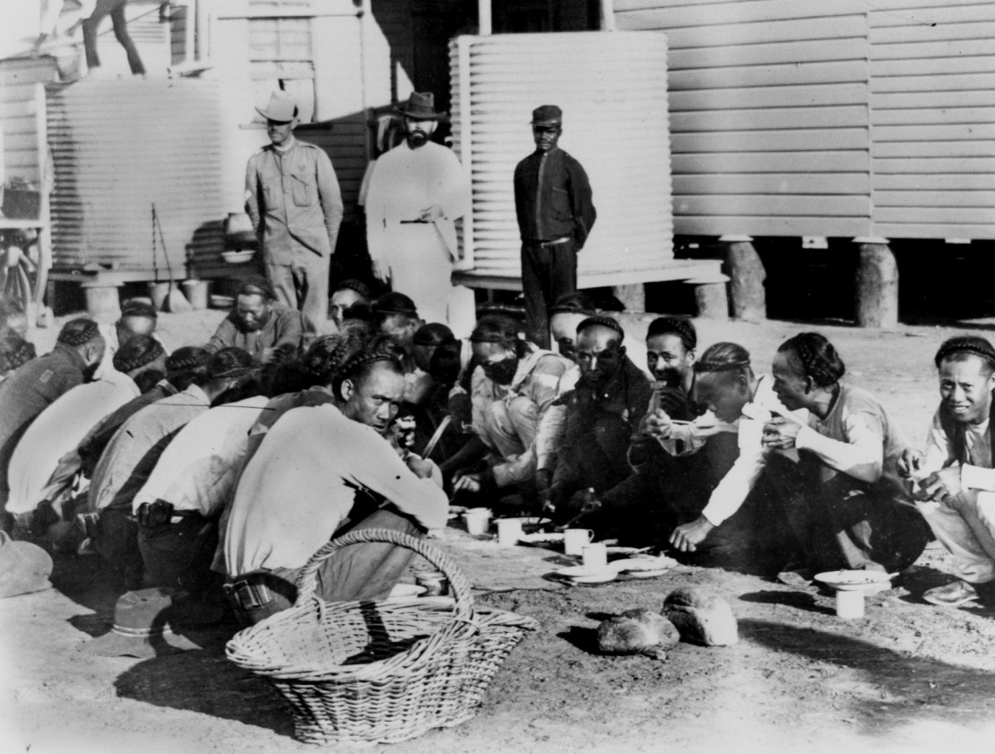 Chinese prisoners being fed under supervision outside in the Goal Yard Burketown Queensland ca October 1900