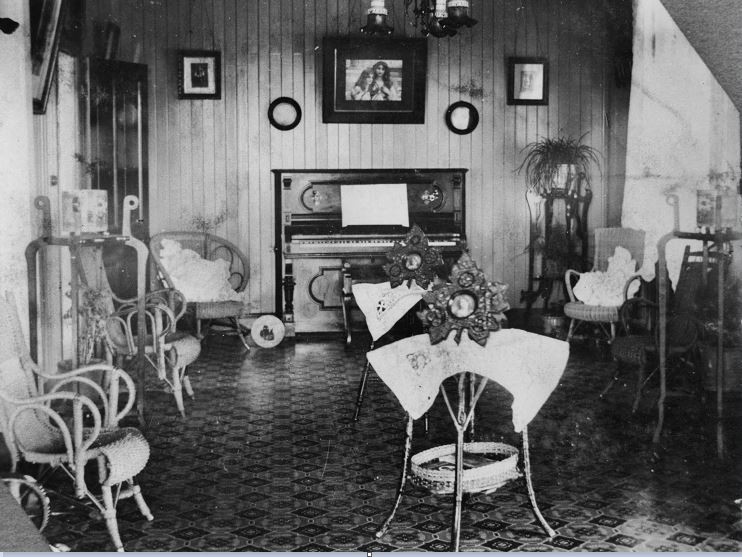 V1-FL56351 Cane furniture and a piano decorate this parlour ca 1915