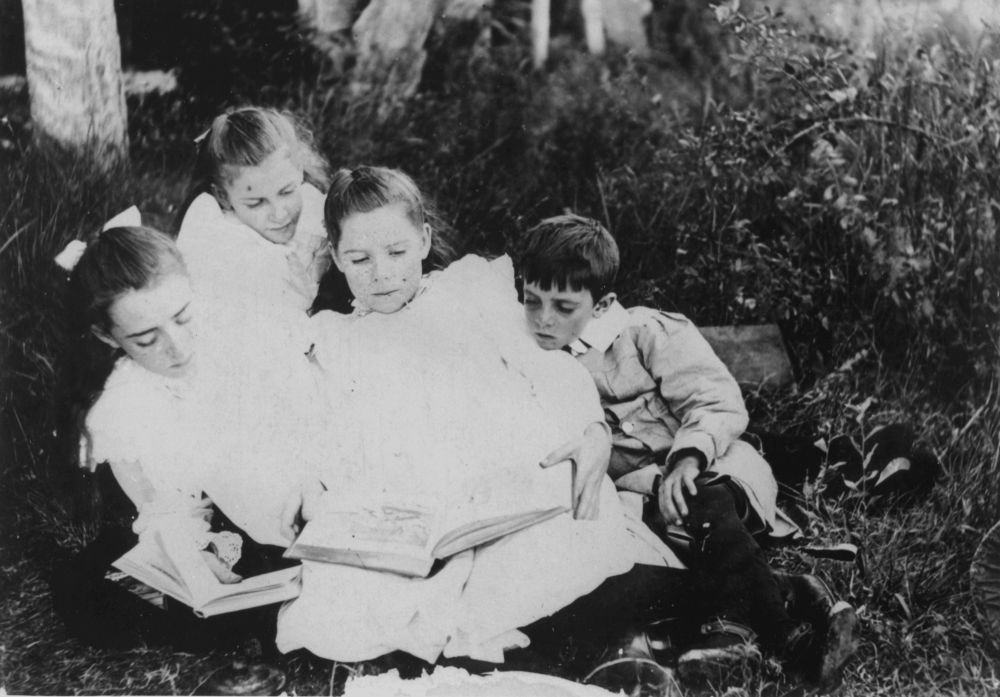 Group of children sitting on the grass reading books 1900-1910 John Oxley Library State Library of Queensland Neg 127410