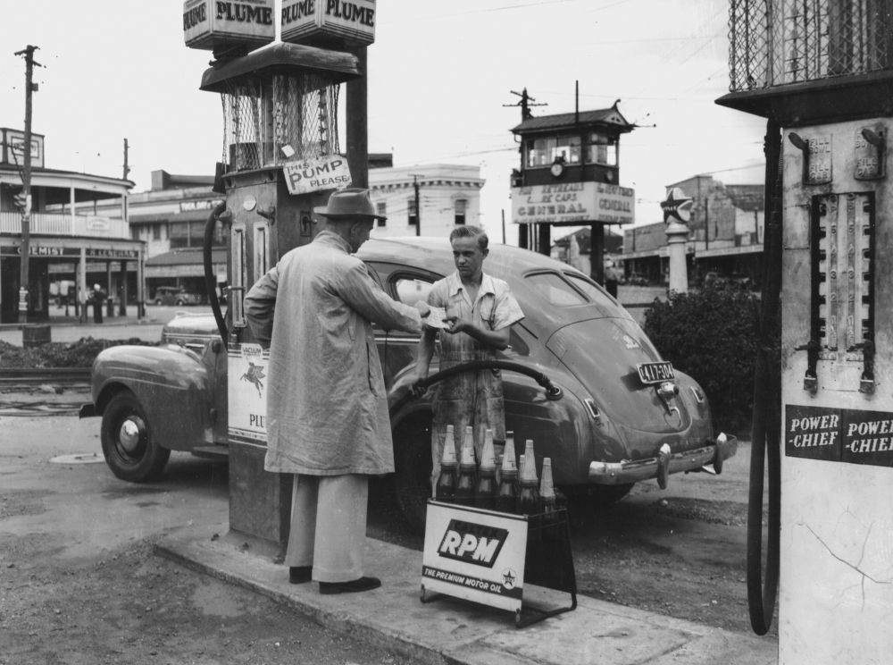 Filling the car with petrol at the Fiveways Woolloongabba1949  Photographer unknown  John Oxley Library SLQ  Negative no 161197