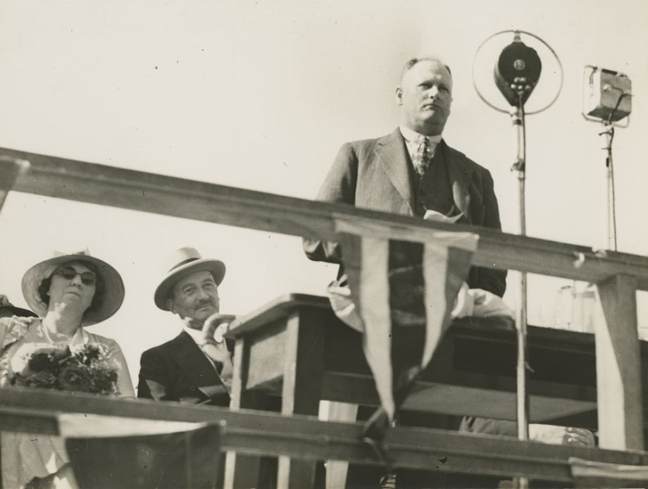 Manuel Hornibrook stands before a large microphone to make a speech on opening day of the Hornibrook Highway The proceedings were also broadcast on radio Sir Leslie Orme Wilson Governor and his wife Lady Wilson are seated behind him
