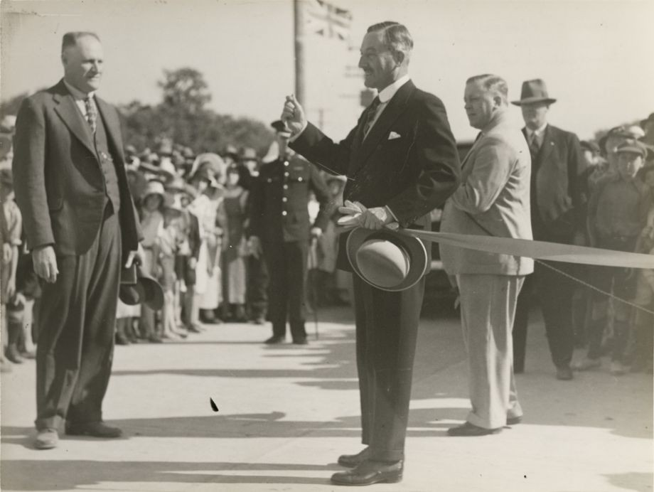 This image looks like the moment when the ribbon has been cut to open the Hornibrook Highway by the Governor Sir Leslie Orme Wilson Standing opposite him is Manuel Hornibrook in a proud moment Manuel gave the Governor a gold boomerang to mark the occasion which was used to cut the ribbon