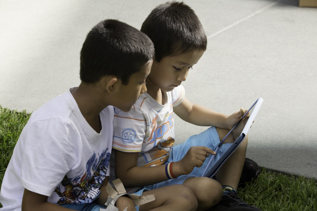 Kids reading on grass 3
