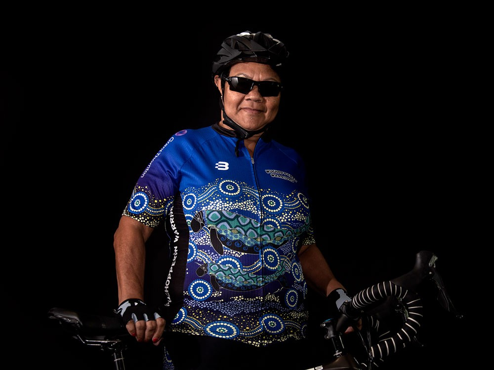 Woman wearing Indigenous sporting shirt and holding a bike