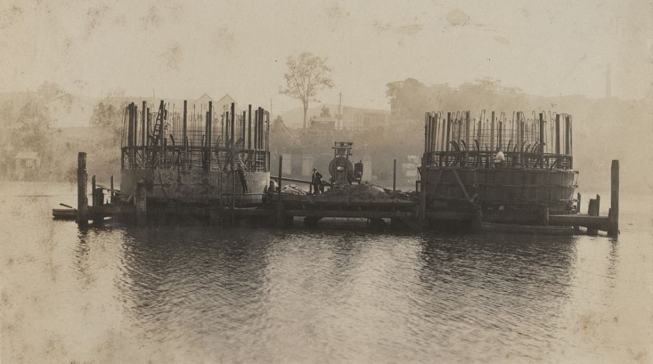 This photo in the Album of the Queensland Cement  Lime Company Limited Photograph Albums shows the caissons being built within the sand-island method This innovative method was designed by Manuel Hornibrook for the unique requirements of sinking the pylons to the Brisbane River bed