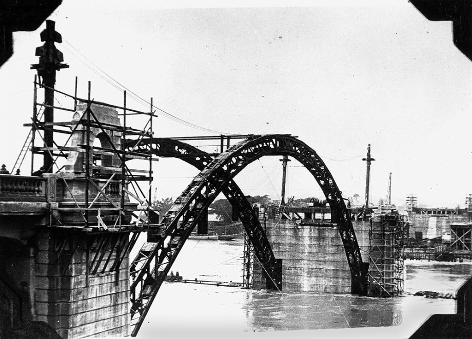 Construction of the William Jolly Bridge then called Grey Street Bridge under construction as the Brisbane River flooded in 1931 photographed 7 February 1931 Each rib of the three spans consisted of structural steel fabricated under a sub-contract by M R Hornibrook Ltd to Evans Deakin and Co Brisbane This steelwork was designed to support the concrete during construction without falsework