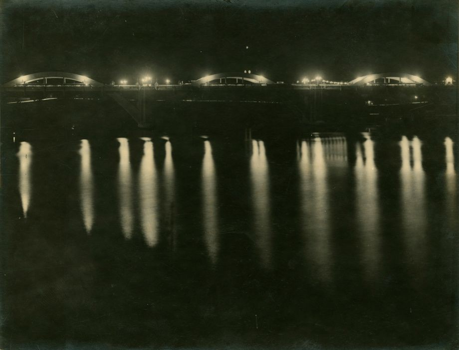 This photo was printed in the Brisbane Courier 3131932 issue and shows the moments after the lights were turned on for the first time on the Grey Street Bridge at the opening event Lady Mayoress Greene turned on the switch and was given a memento of the switch mounted on rosewood as well as an engraved clock by Manuel Hornibrook and Harding Frew