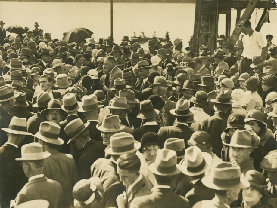 The image shows men and women mingling in the crowd at the opening of the Grey Street Bridge Manuel Hornibrook in centre of photo is one of the few men not wearing a hat on the day