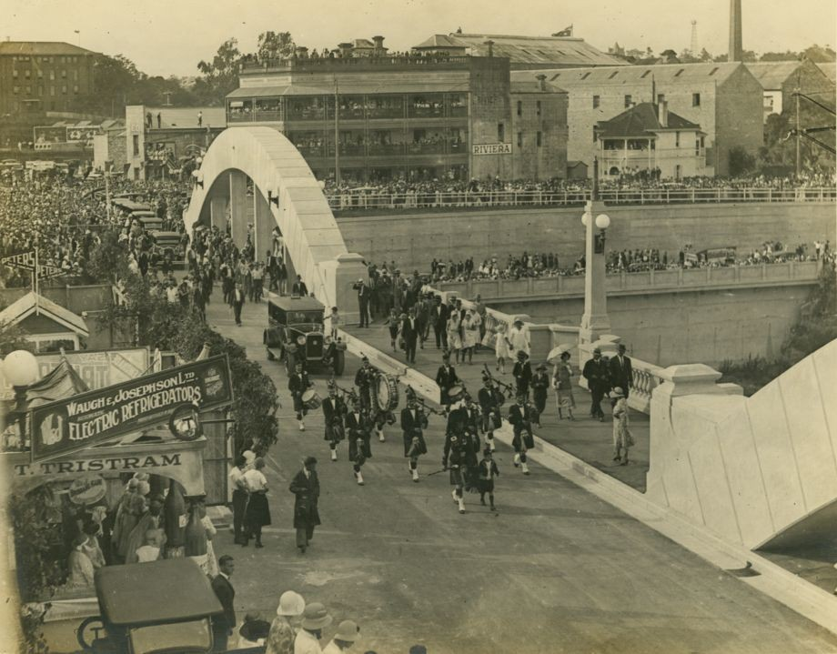 Photo taken as car of the Governor His Excellency Sir John Goodwin leads the procession over the Bridge behind the musicians playing bagpipes after the blue ribbon has been cut Stalls for the festivities include Tristrams and Peters seen in left of photo and other gaily decorated stalls Riviera Hotel seen in background on north side of river