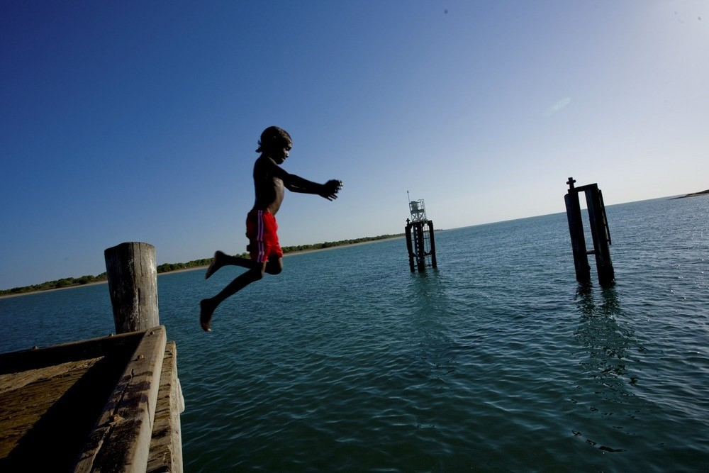 Young boy jumping from wharf into ocean